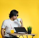 Молодой профессионал наслаждаясь его кофе пока работающ на лете v стоковое изображение rf