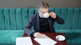 Молодой профессионал работает с контрактом, выпивает кофе на таблице кафа видеоматериал