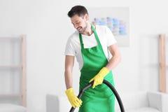 Молодой профессионал с пылесосом внутри помещения стоковое фото