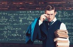 Молодой профессор держа кучу книг рассматривая его стекла Ученый аристократа в коллеже элиты стоковое фото