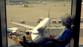 Молодой путешественник, ребенок сидя на окне в авиапорте ждать отключение акции видеоматериалы