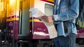 Молодой путешественник стоя около поезда самостоятельно с картой перемещения на платформе в железнодорожном вокзале Стоковые Изображения