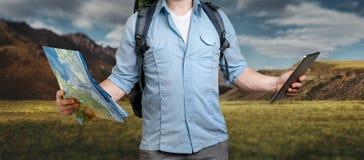 Молодой путешественник с рюкзаком держит бумажные карту и планшет T стоковые изображения