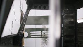 Молодой работник в белой форме красит кабину тележки с машиной спрейера сток-видео