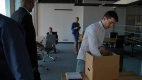 Молодой работник распаковывает коробку с docs и оборудованием Его коллеги идя близко в современный офис акции видеоматериалы