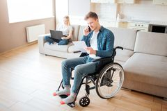 Молодой работник с инвалидностью в комнате Удержание куска бумаги и говорить по телефону Молодая женщина сидит позади на кресле с стоковые изображения