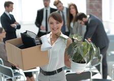 Молодой работник с личными вещами на предпосылке офиса Стоковые Фото