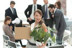 Молодой работник с личными вещами на предпосылке офиса Стоковые Изображения