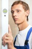 Молодой работник человека плотника с уровнем Стоковое Изображение RF