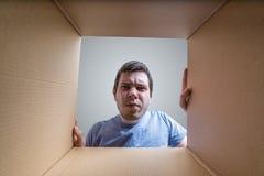 Молодой разочарованный человек смотрит на подарке внутри картонной коробки Стоковые Изображения