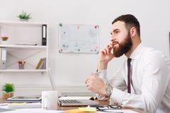 Молодой расслабленный бизнесмен в белой рубашке говоря на черни с компьтер-книжкой в современном белом офисе Стоковое Изображение RF