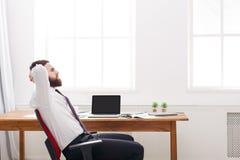 Молодой расслабленный бизнесмен в белой рубашке с компьтер-книжкой в современном белом офисе Стоковые Фотографии RF
