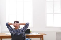 Молодой расслабленный бизнесмен с компьтер-книжкой в современном белом офисе Стоковые Фото
