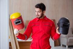 Молодой ремонтник с электродом оружия заварки и weldin шлема Стоковая Фотография