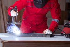 Молодой ремонтник с электродом оружия заварки и weldin шлема Стоковое Изображение