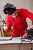 Молодой ремонтник с электродом оружия заварки и weldin шлема Стоковые Изображения