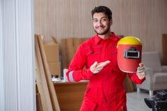 Молодой ремонтник с электродом оружия заварки и weldin шлема Стоковое Фото