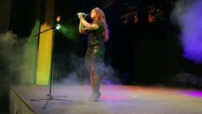 Молодой рост певицы redhead полностью на этапе на микрофоне в слойке дыма акции видеоматериалы
