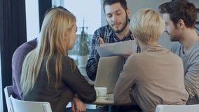 Молодой сердитый человек обсуждая изучение рыночной конъюнктуры с коллегами в встрече Стоковая Фотография RF