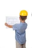 Молодой серьезный построитель читая изолированный план строительства, повернутый назад, на белизне Стоковые Фотографии RF