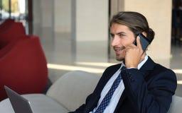 Молодой сидеть бизнесмена ослабил на софе на лобби гостиницы звоня телефонный звонок, ждать кто-то Стоковые Изображения