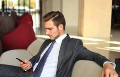 Молодой сидеть бизнесмена ослабил на софе на лобби гостиницы звоня телефонный звонок, ждать кто-то Стоковая Фотография RF