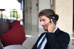 Молодой сидеть бизнесмена ослабил на софе на лобби гостиницы звоня телефонный звонок, ждать кто-то Стоковое фото RF