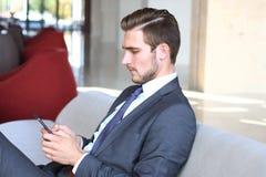 Молодой сидеть бизнесмена ослабил на софе на лобби гостиницы звоня телефонный звонок, ждать кто-то Стоковое Изображение