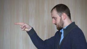 Молодой случайный бородатый палец пунктов человека, который нужно встать на сторону сток-видео