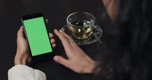 Молодой смартфон пользы бизнес-леди с зеленой сенсорной панелью экрана и конец показывать жестами вверх в кафе Удерживание девушк акции видеоматериалы