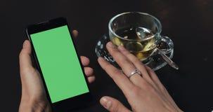 Молодой смартфон пользы бизнес-леди с зеленой сенсорной панелью экрана и конец показывать жестами вверх в кафе Удерживание девушк видеоматериал