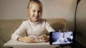 Молодой, смешной блоггер девушки делает показатель вопроса Ребенок распаковывает яйцо с сюрпризом акции видеоматериалы