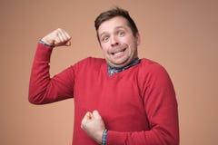 Молодой смешной человек в красном свитере, показывает бицепс изолированный над белой предпосылкой стоковые изображения rf