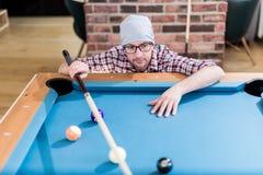 Молодой современный модный человек смотря шарики билльярдов бассейна стоковые изображения