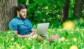 Молодой современный фрилансер бизнесмена работая на компьютере и sitt Стоковое Изображение RF