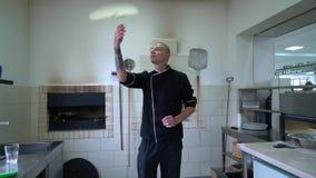 Молодой создатель пиццы подготавливает пиццу в кухне ресторана Кашевар поворачивает тесто в воздухе и распространяет акции видеоматериалы