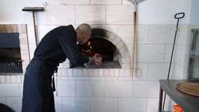 Молодой создатель пиццы подготавливает пиццу в кухне ресторана Кашевар кладет пиццу в горячую печь и поворачивает его сверх видеоматериал