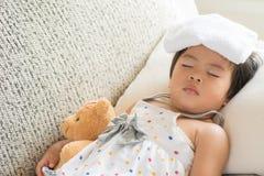 Молодой спать и больной маленькой девочки на софе с более холодным гелем стоковая фотография rf