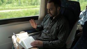 Молодой специалист с наушниками говоря с работодателем через видео-чат используя ноутбук в поезде сток-видео
