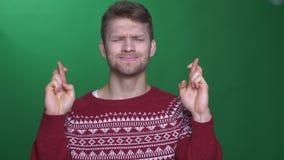 Молодой спортсмен брюнета в свитере делает жест пересекать-пальцев моля для успеха на зеленой предпосылке видеоматериал