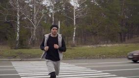 Молодой спортсмен пересекает дорогу, останавливает, проверяет время и продолжает побежать сток-видео