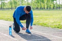 Молодой спортсмен связывая ботинок спорт стоковые изображения