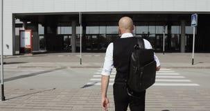 Молодой стильный облыселый бизнесмен идя к деловому центру, авиапорту, офису Концепция: новое дело, путешествуя мир акции видеоматериалы