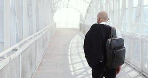 Молодой стильный облыселый бизнесмен идя к деловому центру, авиапорту, офису Концепция: новое дело, путешествуя мир сток-видео