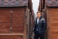 Молодой стильный парень с монументальной стороной идет в крутой город около деревянных и каменных стен стоковые изображения