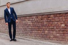 Молодой стильный парень с монументальной стороной идет в крутой город около деревянных и каменных стен стоковое изображение