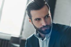 Молодой стильный руководитель бизнесмена внутри помещения на офисе смотря в сторону стоковое фото