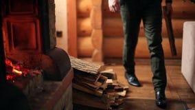 Молодой стильный человек в связанный бросать свитера деревянный входит в систему камин дома Непознаваемый кавказский мужчина клад видеоматериал
