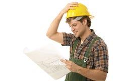 Молодой строитель смотря план пола Стоковое Изображение