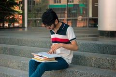 Молодой студент в футболке и стекла читая на стороне записывают стоковые изображения
